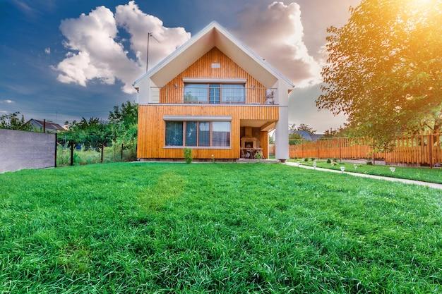Nowoczesny domek letni na tle błękitnego nieba w letnim ogrodzie. słoneczny dzień