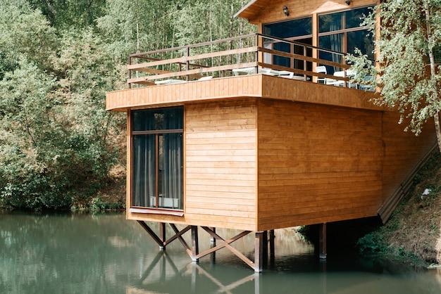 Nowoczesny drewniany dom na poddaszu nad jeziorem, z bliska. na zewnątrz wiejskiego domu z balkonem, domek na wodzie w pobliżu lasu, letni dzień.