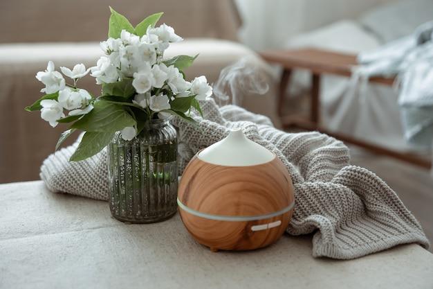 Nowoczesny dyfuzor zapachu olejków w salonie na stole z dzianinowym elementem i kwiatami.