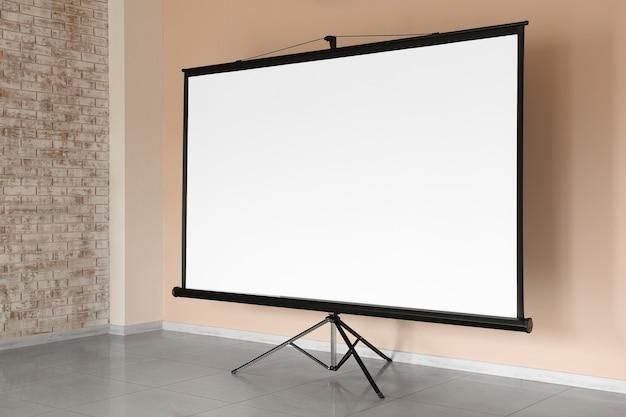 Nowoczesny ekran do projektora przy ścianie w pomieszczeniu