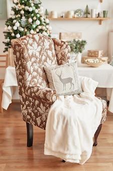 Nowoczesny fotel bujany z dywanikiem. przytulny fotel z pledą i poduszką przy ścianie z cegły stylowy wystrój wnętrz. boże narodzenie, fotel z pledem i poduszką.