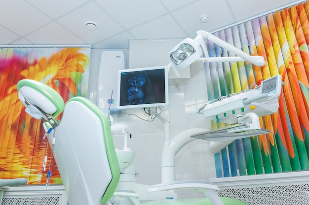 Nowoczesny gabinet stomatologiczny z krzesłem i profesjonalnym komputerowym systemem anestezjologicznym.