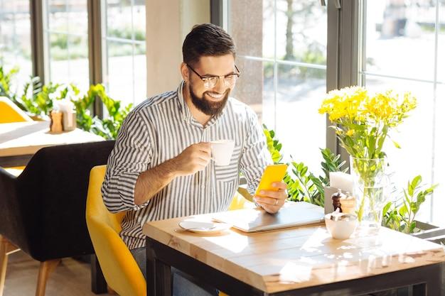 Nowoczesny gadżet. wesoły miły człowiek siedzący ze swoim smartfonem podczas picia kawy w stołówce
