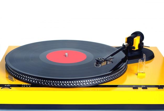Nowoczesny gramofon w srebrnej obudowie z obrotową płytą winylową z czerwoną etykietą