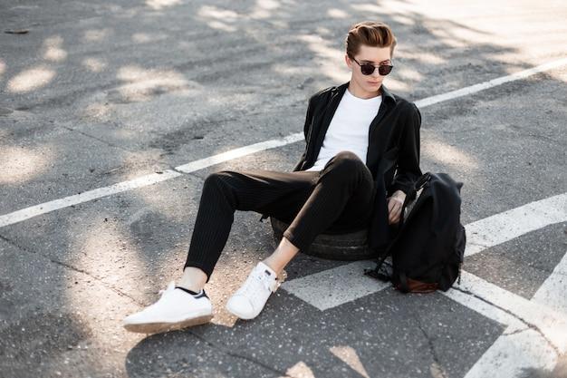 Nowoczesny hipster młody człowiek w eleganckie czarne ubrania w białych modnych trampkach z plecakiem w okularach przeciwsłonecznych siedzi