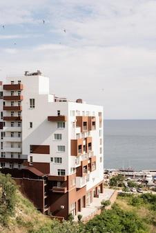 Nowoczesny hotel lub apartamentowiec nad morzem. piękny letni krajobraz nadmorski, port dla łodzi