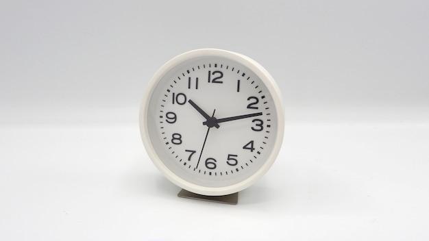 Nowoczesny i czysty zegar w białym kolorze z wskazówką minutową i godzinową