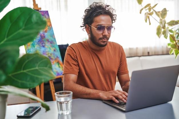 Nowoczesny i wygodny pokój biurowy. profesjonalny indyjski freelancer skoncentrowany na swojej pracy korzysta w domu z laptopa.