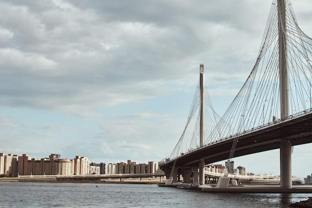Nowoczesny kabel został mostem nad rzeką przed pochmurnym niebem. zbliżenie budowy inżynierii