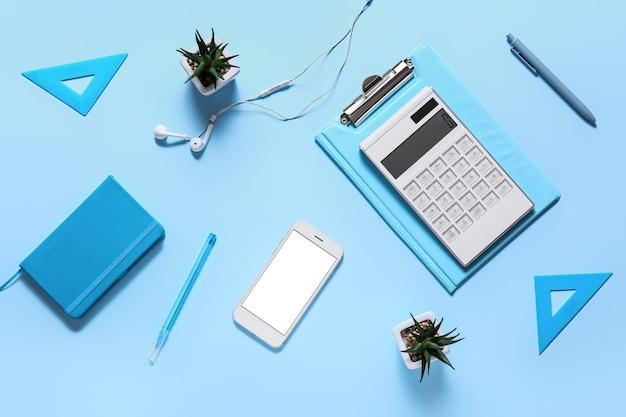 Nowoczesny kalkulator i artykuły biurowe z telefonem komórkowym na kolorowej powierzchni