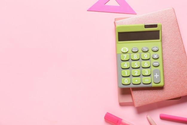 Nowoczesny kalkulator i papeteria na kolorowej powierzchni