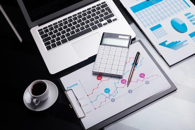 Nowoczesny kalkulator to notatnik i arkusz z harmonogramem obok filiżanki kawy