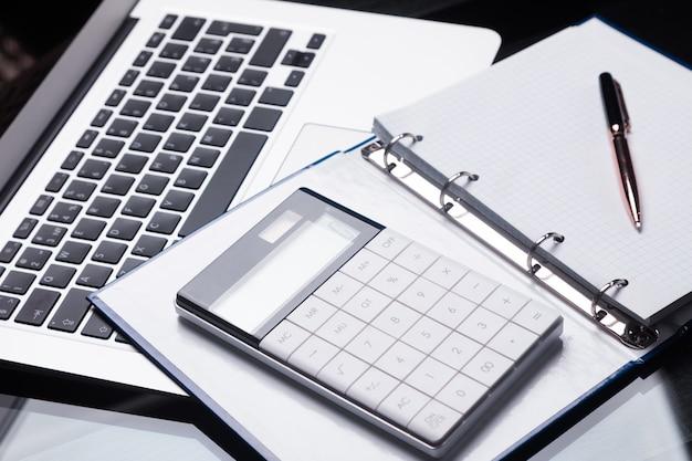 Nowoczesny kalkulator znajduje się na laptopie i otwartym notatniku