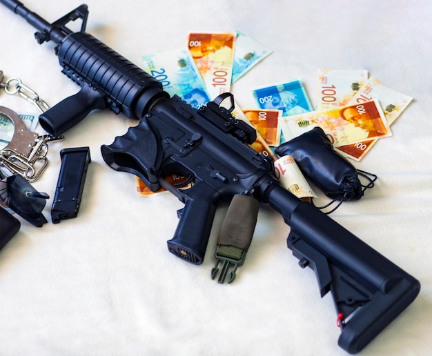 Nowoczesny karabin automatyczny, amunicja do pistoletu, pistoletu i nabojów 9mm, kajdanki na izraelskie nowe szekle i banknoty w dolarach amerykańskich. karne pieniądze i kara, miejsce kopiowania. baner przestępstwa finansowego
