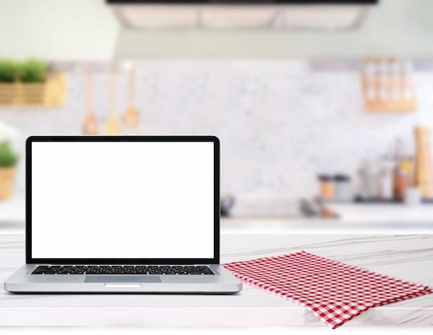 Nowoczesny komputer, laptop z pustym ekranem na drewnianym blacie na niewyraźnym tle kuchni kitchen