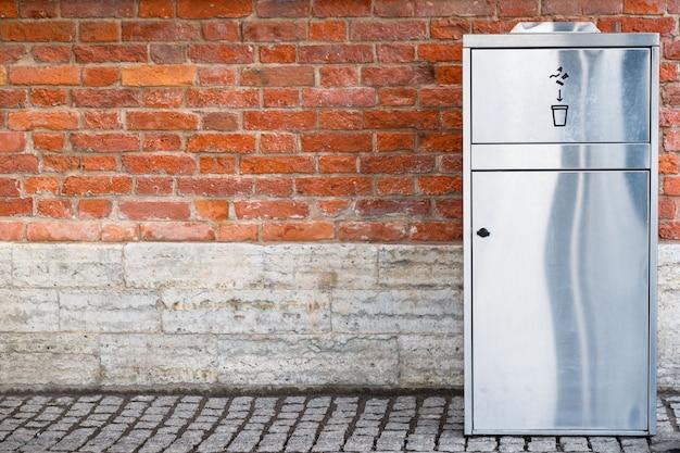 Nowoczesny kosz na śmieci ze stali nierdzewnej / metalu do recyklingu plastikowych i papierowych kubków na ścianie z cegły na zewnątrz