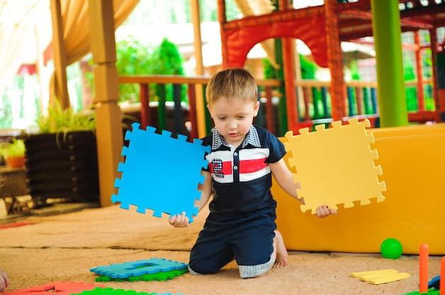 Nowoczesny kryty plac zabaw dla dzieci. chłopiec bawi się na placu zabaw.