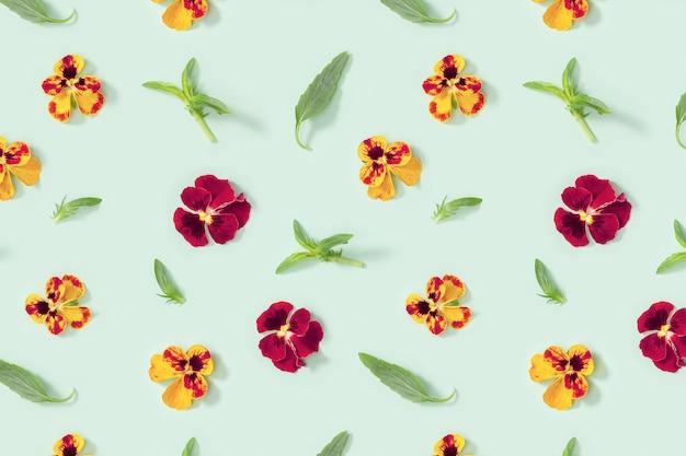 Nowoczesny kwiatowy wzór z żółto-czerwonymi kwiatami bratek, zielonymi liśćmi, małe letnie kwieciste stylizacje sezonowe