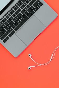 Nowoczesny ładny notatnik i białe słuchawki na czerwonej powierzchni