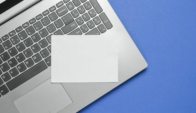 Nowoczesny laptop i arkusz białego papieru do kopiowania miejsca na niebieskim tle. widok z góry