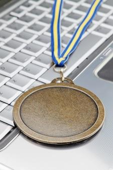 Nowoczesny laptop i nagrodzony złotym medalem za sukces. zbliżenie.