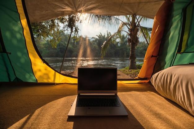 Nowoczesny laptop otwiera się i odstawia w namiocie kempingowym w parku przyrody o zachodzie słońca