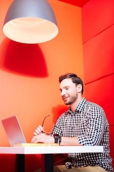 Nowoczesny laptop. spokojny atrakcyjny młody freelancer siedzi w czerwonym wnętrzu i uśmiecha się, patrząc na ekran nowoczesnego laptopa