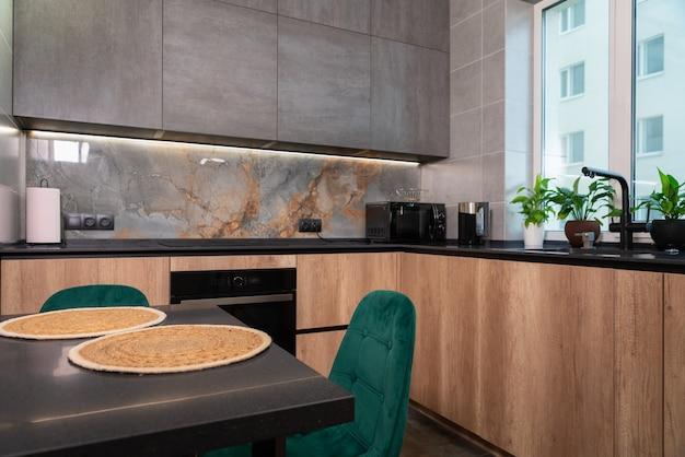 Nowoczesny luksusowy wystrój wnętrza kuchni w mieszkaniu miejskim z zabudowanymi szafkami, centralną wyspą na jadalnię i kamiennymi powierzchniami roboczymi na drewnianych szafkach