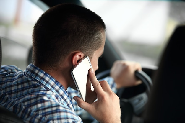 Nowoczesny mężczyzna rozmawia przez smartfona, siedząc w samochodzie