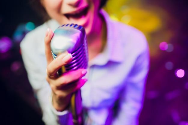 Nowoczesny mikrofon do śpiewania w pięknym rozmytym kolorze bokeh.