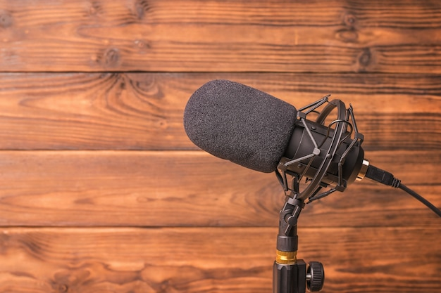 Nowoczesny mikrofon na stojaku na drewnianym stole. sprzęt do nagrywania dźwięku.