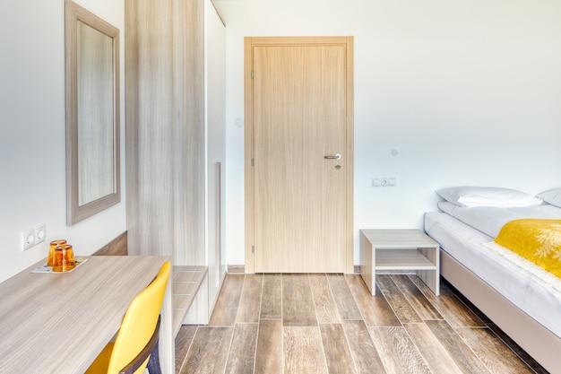 Nowoczesny minimalistyczny pokój hotelowy z zamkniętymi drzwiami do łazienki, lustrem, okularami, żółtym krzesłem i szafą