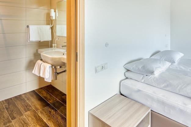 Nowoczesny minimalistyczny pokój hotelowy z zamkniętymi drzwiami do łazienki, lustrem, poduszką, umywalką i ręcznikami