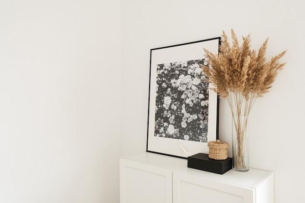 Nowoczesny minimalistyczny skandynawski wystrój wnętrz w stylu nordyckim. komoda, ramki na zdjęcia, palma i dekoracje
