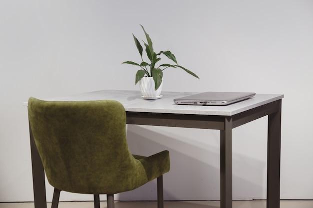 Nowoczesny minimalistyczny zielony welurowy fotel do pracy i loftowy stolik z laptopem