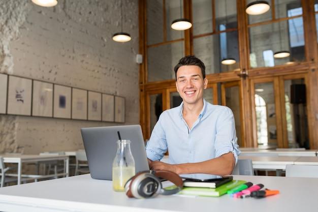 Nowoczesny młody człowiek pewny siebie pracujący na laptopie