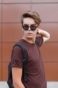 Nowoczesny młody hipster mężczyzna z modną fryzurą w czarnych stylowych okularach przeciwsłonecznych w letniej koszulce z czarnym sportowym plecakiem stoi na zewnątrz w pobliżu ściany vintage