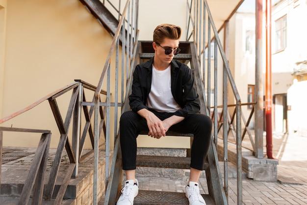 Nowoczesny młody hipster modne okulary przeciwsłoneczne w stylowej czarnej koszuli