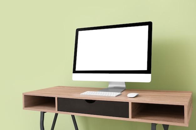 Nowoczesny monitor pc na stole w pobliżu kolorowej ściany