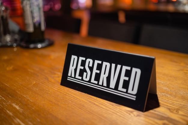 Nowoczesny pomysł na zarezerwowany stolik z napisem rezerwacja twojego miejsca. idea restauracji napis zarezerwowany na drewnianym stole w kawiarni.