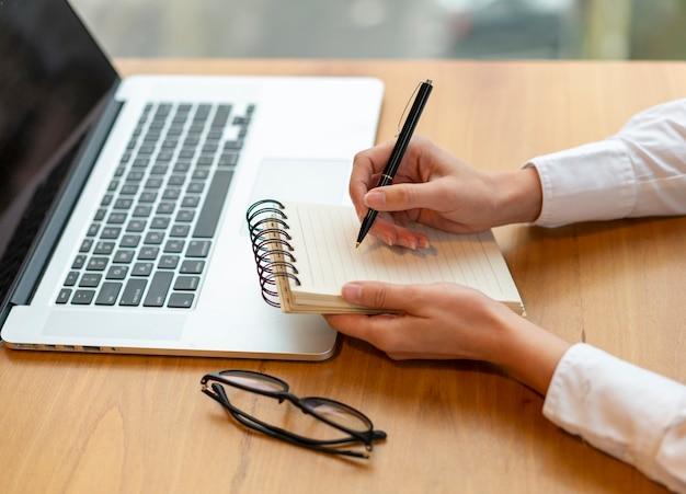 Nowoczesny pracownik pisze w notatniku