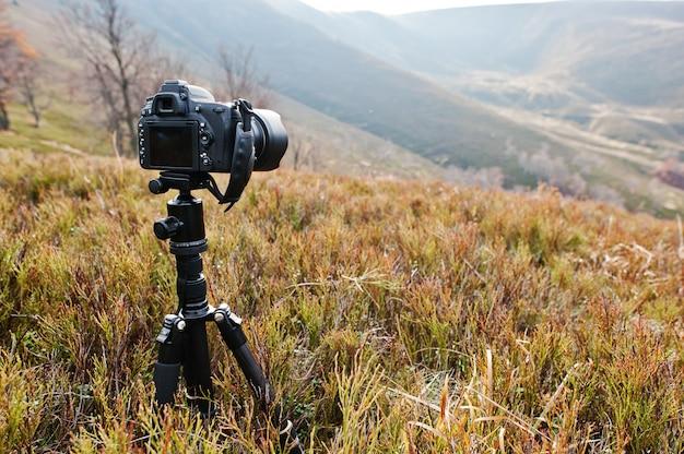 Nowoczesny profesjonalny aparat dslr na statywie, fotografia plenerowa w dzikiej przyrodzie. góry w tle.