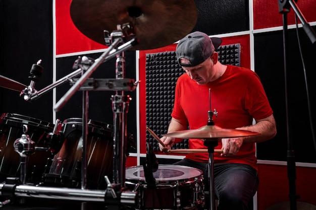 Nowoczesny, profesjonalny perkusista gra na perkusji w bazie prób, czerwono-czarnym studiu nagraniowym