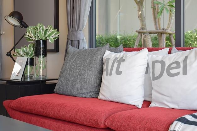 Nowoczesny projekt salonu z poduszkami na czerwonej kanapie i dekoracyjną lampą