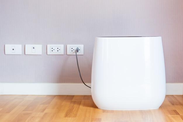 Nowoczesny przenośny oczyszczacz powietrza w pokoju z bliska.