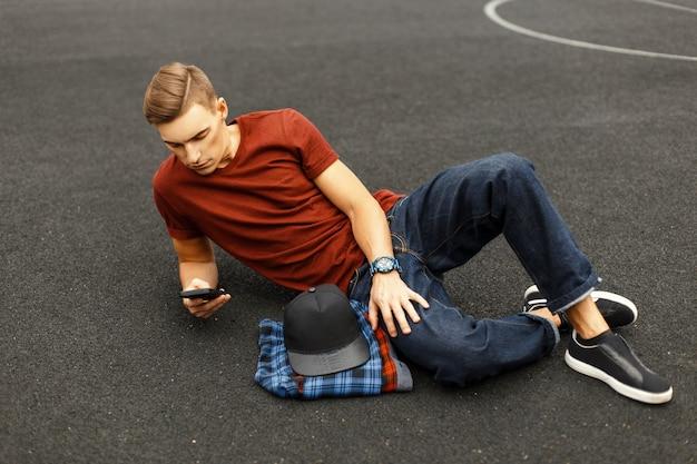 Nowoczesny, przystojny mężczyzna używa telefonu i leży na chodniku.