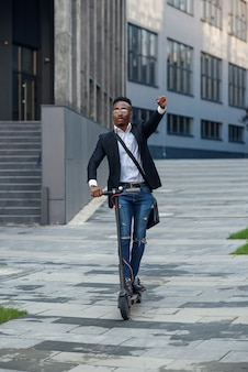 Nowoczesny radosny biznesmen afroamerykański jeździ skuterem elektrycznym po zakończeniu dnia pracy