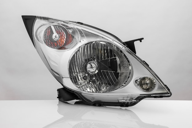 Nowoczesny reflektor samochodowy z odbiciem na jasnym tle