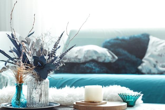 Nowoczesny salon, ze sztucznymi kwiatami w wazonie i elementami wystroju domu na drewnianym podświetlanym stoliku.