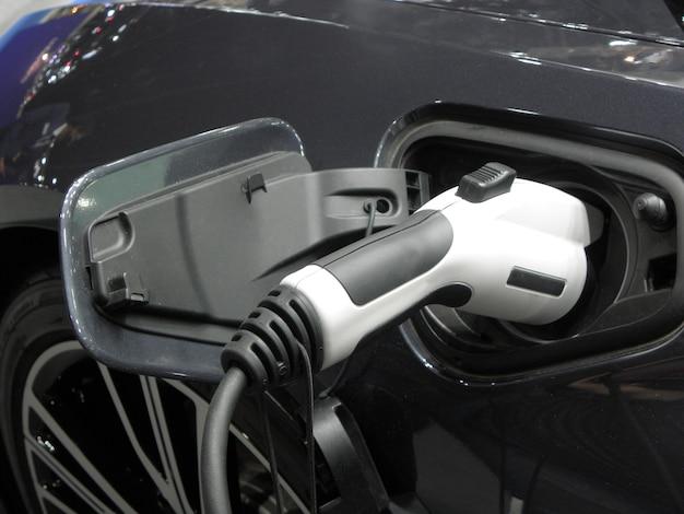 Nowoczesny samochód elektryczny w kolorze białym na ładowaniu z sieci. ekologiczny transport przyszłości